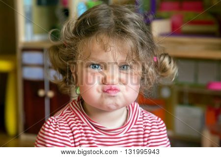Funny portrait of adorable baby girl. Child makes grimaces face