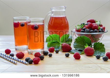 Left two glasses of berries compote near bowl with berries carafe compote on a light wooden background scattered berries and some empty space . Fresh berries compote and empty space. Horizontal.