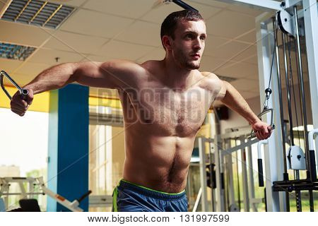 Young strong man with torso is doing flys on cable crossover in gym