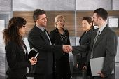 Happy businesspeople shaking hands greeting each other before business meeting in office. poster
