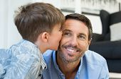 Young little boy giving a kiss on father cheek. Cute child kissing her dad at home. Loving son playing with his father. poster