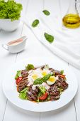 Veal beef fillet medallions warm salad with tomatoes, cucumber, cream sauce, basil and eggs. Restaraunt menu meal in white plate on table background. poster