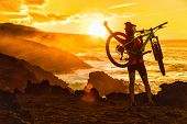 Success, achievement, accomplishment and winning concept with cyclist mountain biking. Happy MTB woman cycling raising arms lifting bike by sea during sunset cheering and celebrating at summit top. poster