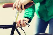 people, vehicle, eisure and lifestyle - close up of man adjusting fixed gear bike saddle high poster