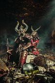Couple of fantasy knights in armor with axe. Catacombs on the background. poster