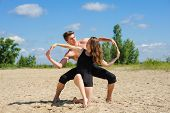 Contemporary dance. Man and woman in passionate dance pose on beach. Young couple dancing modern dance outdoors. Man and woman hands showing infinity symbol. Man with naked torso on sand. poster