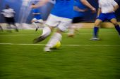 a soccer game in motion with the movement to prove it. poster