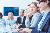 Young businesspeople evolving new company strategy during business meeting in office poster