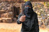 Terrorism concept. Terrorist threatening with knife in desert. poster