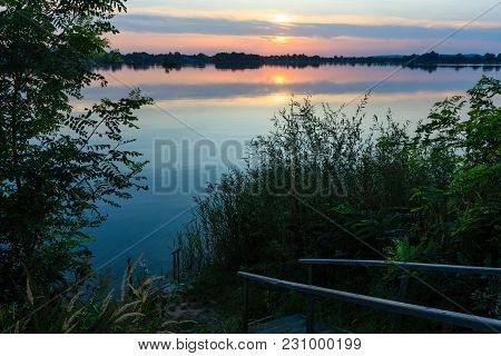 Wooden Stairs To The Picturesque Summer Evening Sunset Lake Shore. Concept Of Tranquil Country Life,