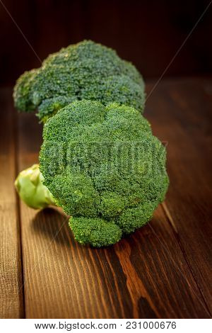 Big And Ripe Broccoli Florets On Wooden Table