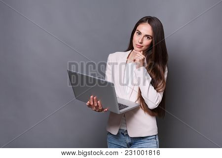 Smart Solutions. Beautiful Thoughtful Business Woman With Hand On Chin At Gray Studio Background Sta