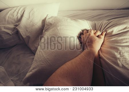 Man Squeezes Woman Hand On White Sheets. Passion While Making Love