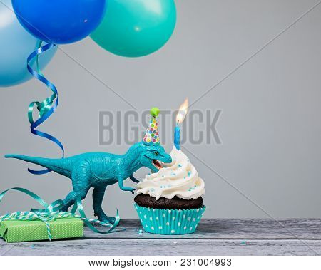 Blue Dinosaur Toy Eating A Birthday Cupcake  On A Gray Background.