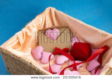 Wicker With Valentines Day Gifts: Closed Jewelry Box, Old Craft Paper Envelope And Pink Heart Shapes
