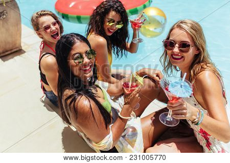 Group Of Women Hanging Out By The Pool With Drinks