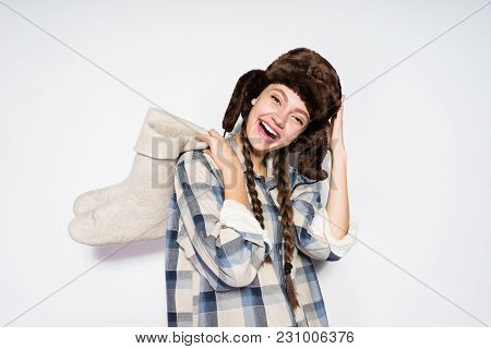 Happy Beautiful Russian Girl With Pigtails, In A Warm Hat Waits For Winter, Holds Warm Felt Boots An