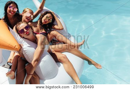 Women Floating Together On A Big Inflatable Toy In Pool