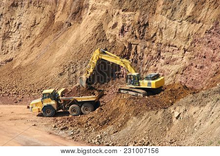 A Backhoe And Dumptruck At Rock Quarry