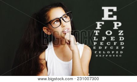 Beautiful Woman Face With Eyeglasses On The Background Of The Table For Vision.