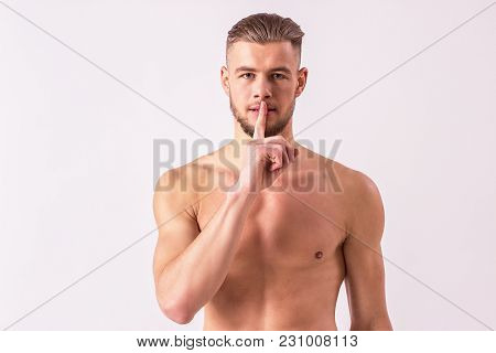 Studio shot of young naked man keeping index finger by lips while standing isolated on white background. Handsome shirtless hipster man gesturing against white background. Natural male beauty