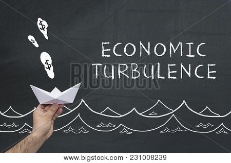Man Holding Paper Ship On Blackboard With Words: Economic Turbulence