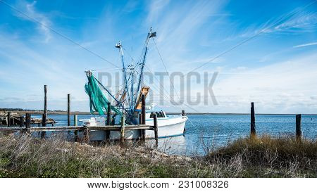 Fishing Boat With Green Nets And Outriggers Docked On The North Caroina Coast With Sunes In The Fore