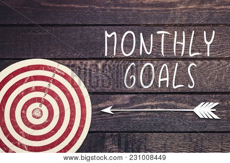Monthly Goals Concept With Dart Board On Dark Wooden Wall.