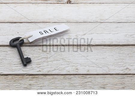 Key And Keyring With The Word Sale Over White Wooden Table