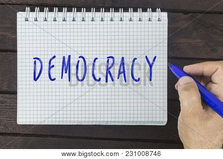 Human Hand Writing On Notepad Inscription: Democracy