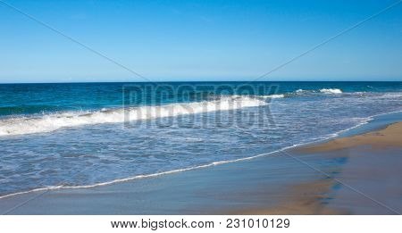 A Calm Blue Sea Against A Blue Sky. A Wave With White Foam On The Sandy Shore. Relax On The Beach On