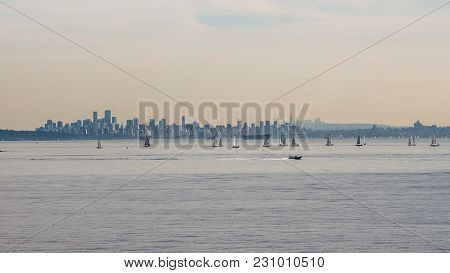 Plenty Of Yachts On The Ocean In Front Of The Big High Rise Modern City Far Away In The Horizon