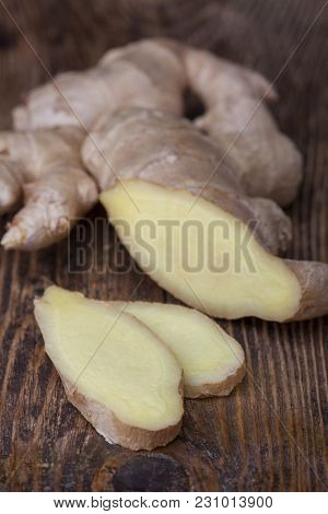 Closeup Of Slices Of Ginger On Dark Wood
