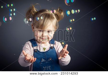 lovely female child play with soap bubbles studio shot portrait
