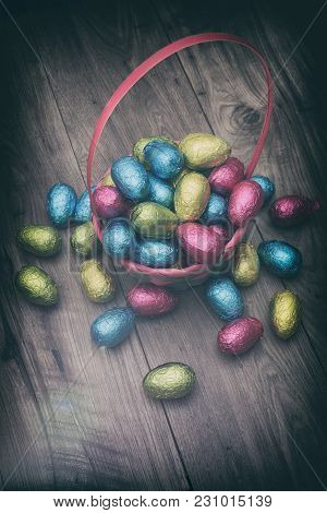 Straw Basket Filled With Easter Chocolate Eggs Wrapped In Colorful Tinfoil On Top Of A Wooden Table