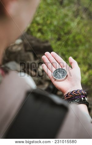 Women Looked At The Compass In Her Hand To Find Right Direction.