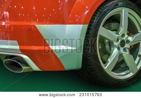 Wheel With Titanium Disc And A Racing Tire And The Rear Bumper Section And Trunk Of A Red Sports Car