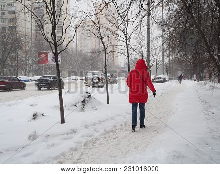 Kiev - Ukraine - March 2018: Person In A Red Down Jacket Walks Along A Snow-covered Street On The Fi