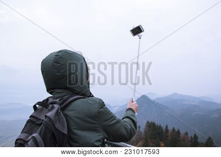 A Young Teenage Girl Makes Selfie On The Phone With A Selfie Stick Against The Background Of A Beaut