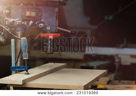 Close-up Of Vertical Drilling Machine With Wooden Plank Pattern In Workshop With Copyspace