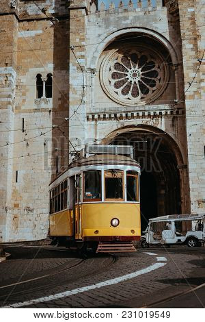 Quaint Yellow Tram Passes Directly In Front Of The Se Cathedral In Lisbon. Lisboa Lissabon.