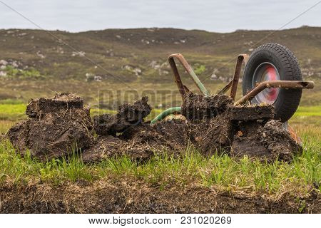 Inverasdale, Scotland - June 9, 2012: Closeup Of Turned Over Rusty Wheel Barrel At Peat Digging Site
