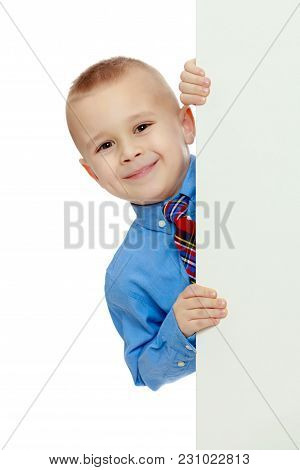 Beautiful Little Boy In A Blue Shirt And Tie Peeking From Behind The Banner.isolated On White Backgr