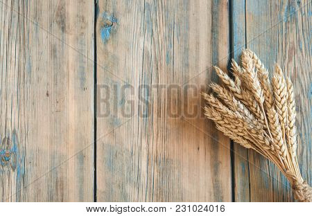 Sheaf of wheat ears on wooden table