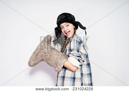 Happy Young Russian Girl In Fur Hat Waiting For Winter, Holding Gray Felt Boots