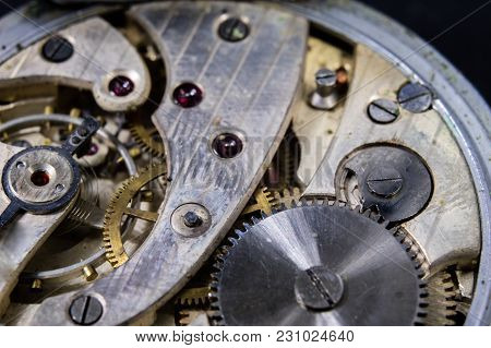 An Old Watch On A Dark Table. Timer Mechanism Seen Enlarged.