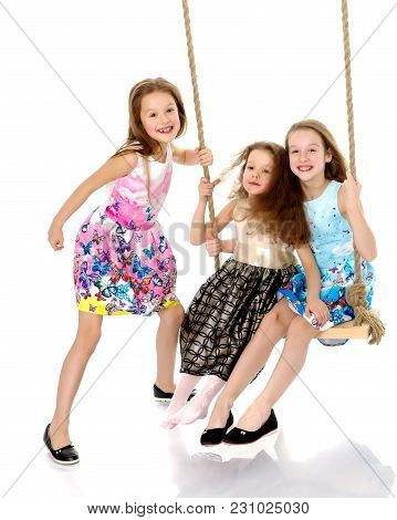 Funny Little Girls Swing On A Swing. The Concept Of A Good Mood, A Happy Childhood. Isolated On Whit