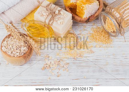 Honeycomb, Sea Salt, Oats And Handmade Soap With Honey On White Rustic Wooden Background. Natural In