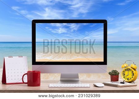 Modern Desktop Computer, Coffee Cup, Alarm Clock, Notebook And Calendar On Wooden Table And View Of