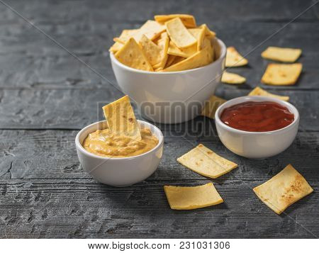 Mexican Tortilla Chips In A Bowl With Sauce And Mustard On The Table. A Dish Of Mexican Cuisine.